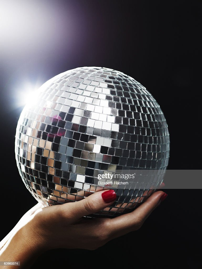 Hands holding small mirror ball up towards light : Stock Photo