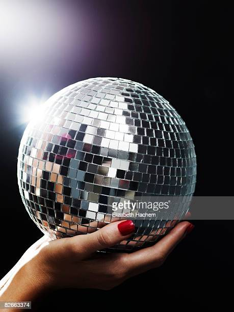 Hands holding small mirror ball up towards light