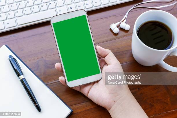 hands holding smart phone with green screen - chroma key foto e immagini stock