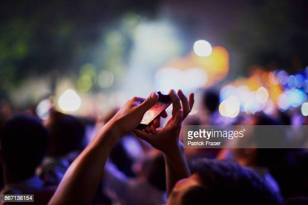 Hands holding smartphone reach up to take picture of fireworks show