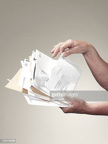 Hands holding stack of letters and bills