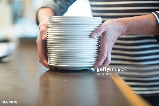 Hands holding stack of plates, saucers