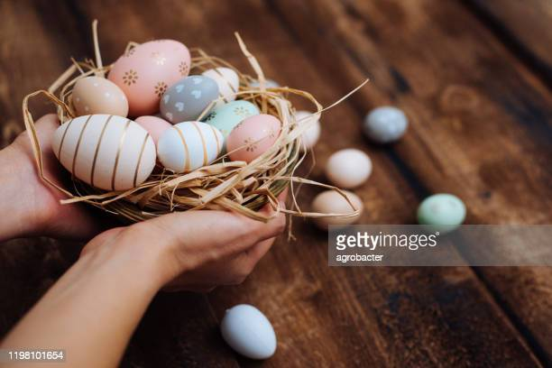hands holding stylish easter eggs - easter egg stock pictures, royalty-free photos & images