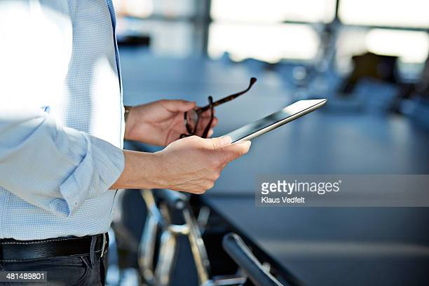 Hands holding tablet & a pair of glasses