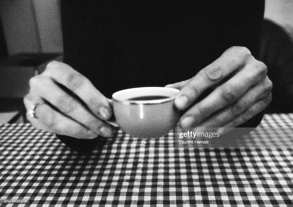 Hands holding teacup, close-up, b&w : Stockfoto