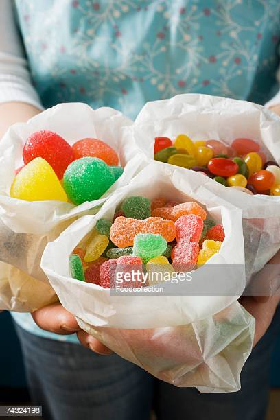 Hands holding three paper bags of jelly sweets