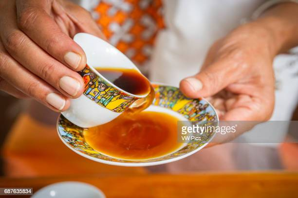 Hands holding traditional Ethiopian coffee cup pouring coffee into saucer