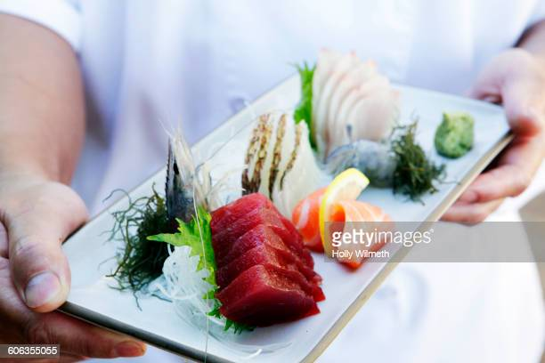 hands holding tray of fresh sushi - pacific islands stock pictures, royalty-free photos & images