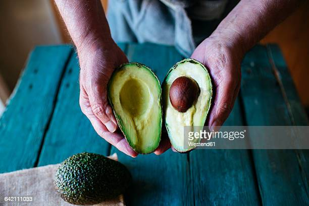 Hands holding two halves of an avocado