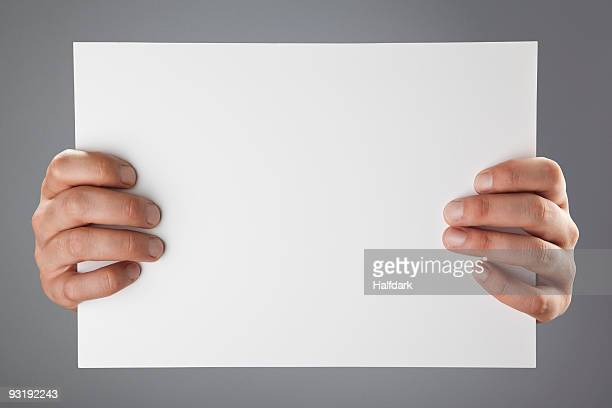 Hands holding up a white piece of paper