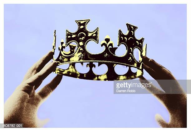 hands holding up crown, close-up (toned b&w) - crown close up stock pictures, royalty-free photos & images