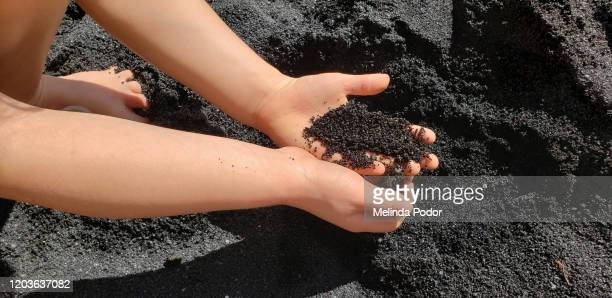 hands holding volcanic sand on the island of hawaii - punalu'u_beach stock pictures, royalty-free photos & images