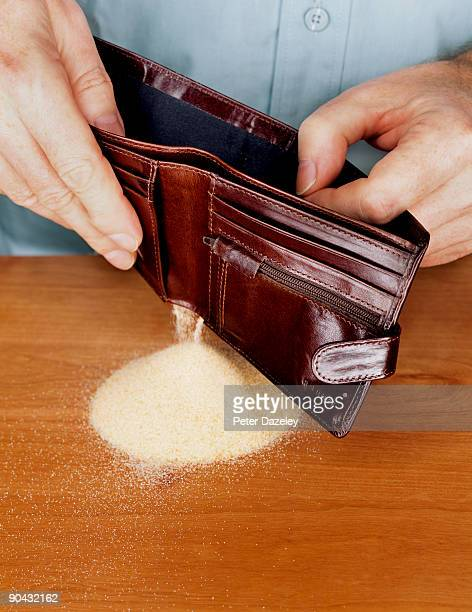 Hands holding wallet with sand pouring out