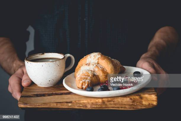 Hands holding wooden tray with continental breakfast croissant and coffee cup