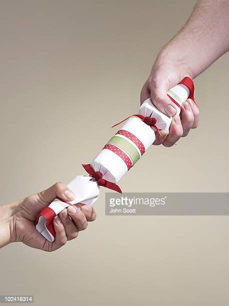 hands holding/pulling a christmas cracker - クリスマスクラッカー ストックフォトと画像