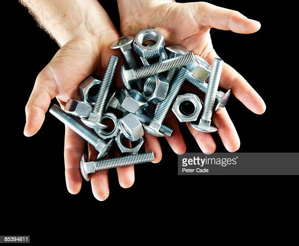 hands holing metal screws and bolts - fastening stock pictures, royalty-free photos & images