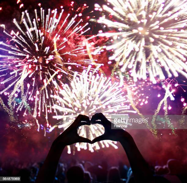 Hands in a heart shape at firework display
