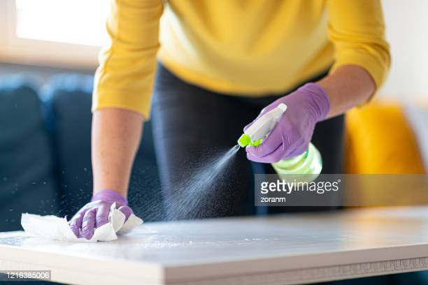 hands in gloves disinfecting coffee table - spray bottle stock pictures, royalty-free photos & images