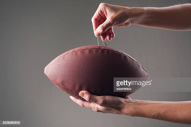 Hands Inserting a Pin Into Football To Deflate It