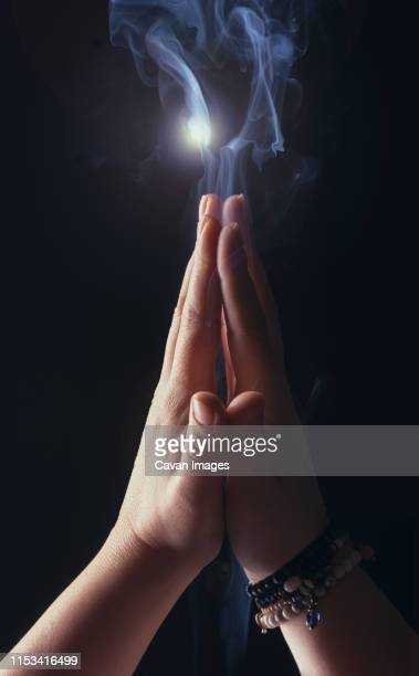 hands joined by the woman who prays - cult stock pictures, royalty-free photos & images
