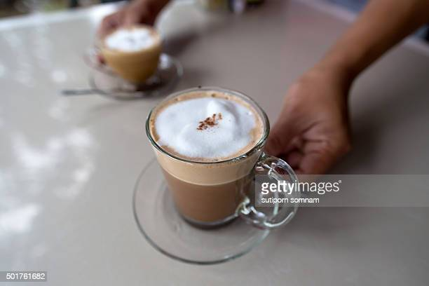 Hands keep coffee cup at table