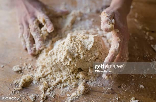 hands kneading homemade dough - mehl stock-fotos und bilder