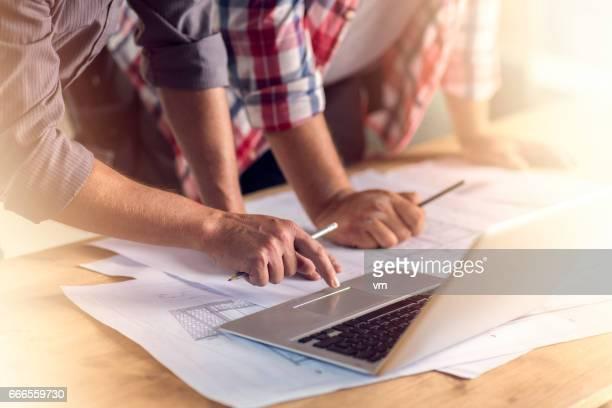 Hands, laptop and blueprints
