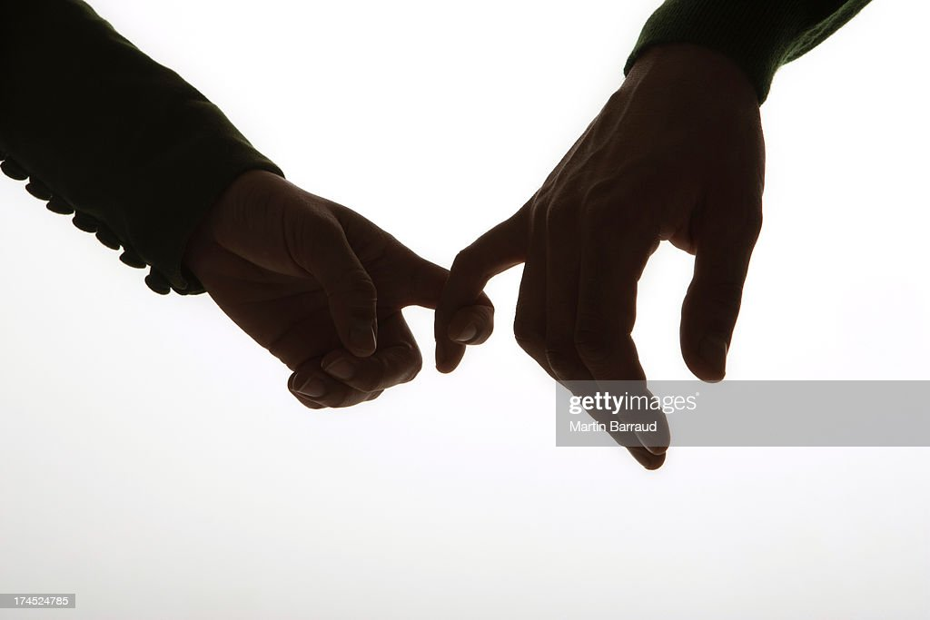 Hands linked by pinky fingers : Stock Photo