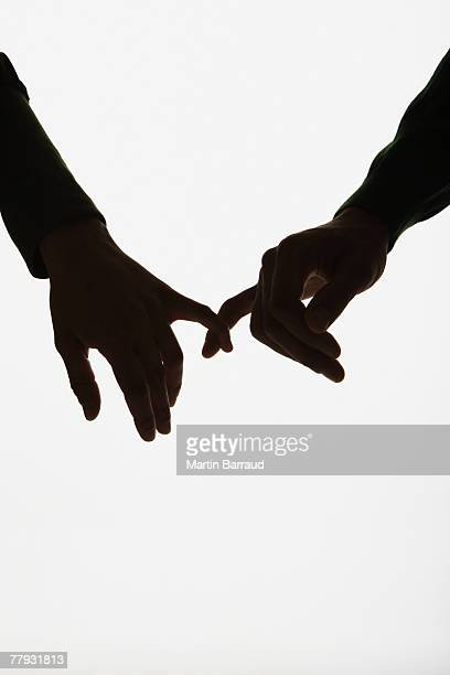 Hands linked by pinky fingers