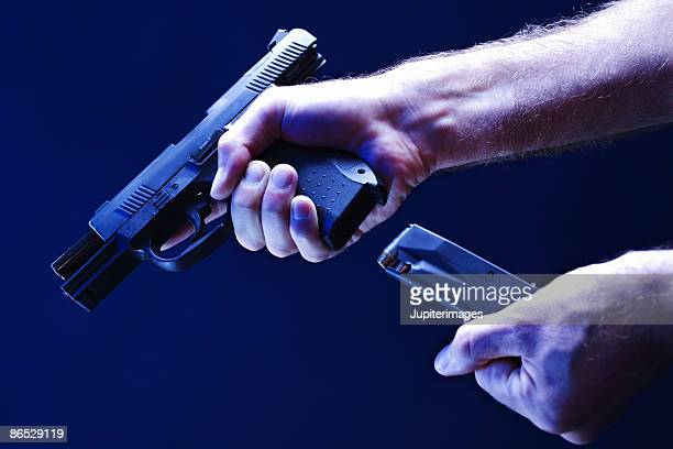 hands loading magazine into handgun - ammunition magazine stock photos and pictures