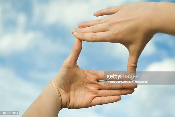 Hands making a finger frame in front of sky