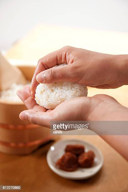 Hands making a rice ball