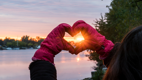 Hands Making Heart Shape around beautiful Sunset wearing Pink gloves - Winter Solstice Love Landscape over water 898355082