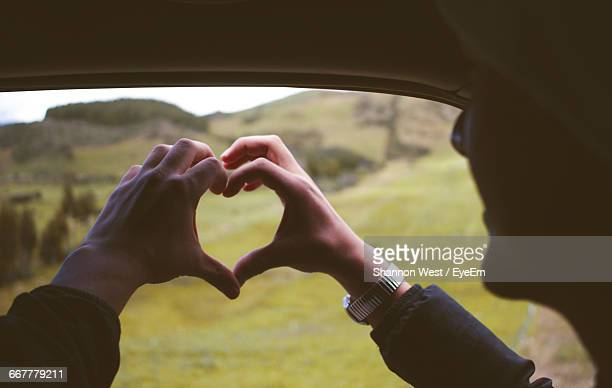 Hands Making Heart Shape In Car