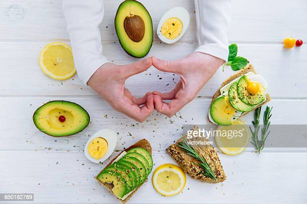 Hands making heart shape with avocado open sandwiches