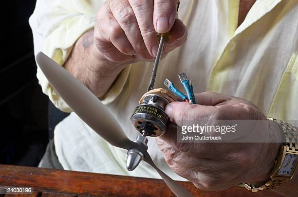 Hands making model aeroplane
