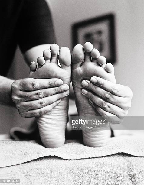 hands massaging woman's feet - foot massage stock pictures, royalty-free photos & images