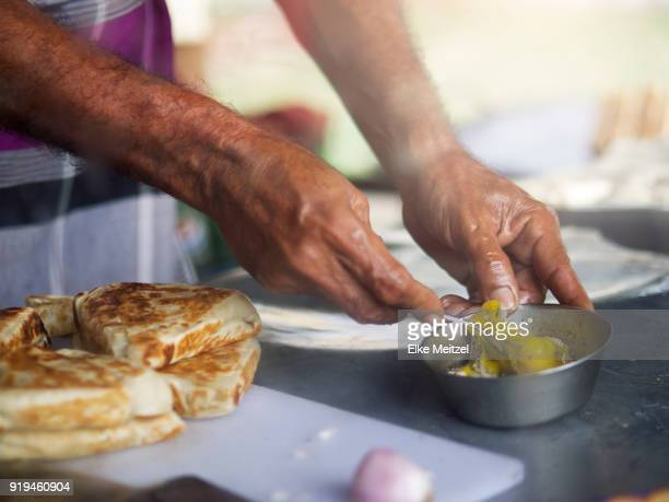 hands mixing and preparing food at food stall - samosa stock photos and pictures