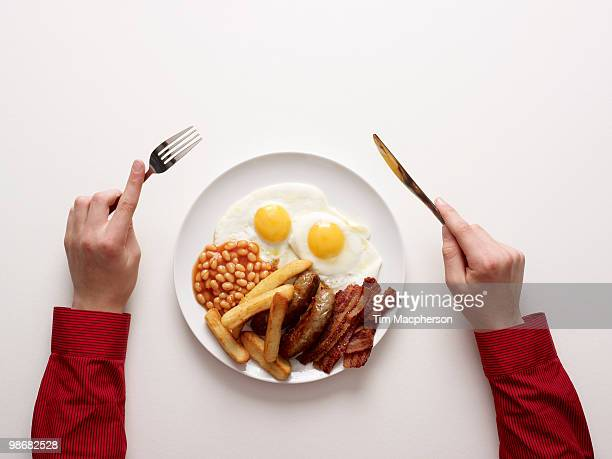 hands next to a fried breakfast