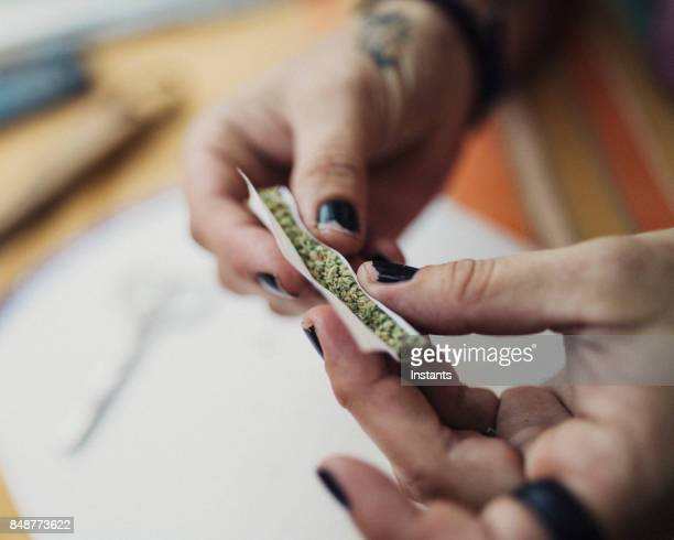 Hands of a 40 year old woman rolling a joint, prescribed by a doctor for her chronic illness.