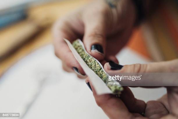hands of a 40 year old woman rolling a joint, prescribed by a doctor for her chronic illness. - weed stock photos and pictures