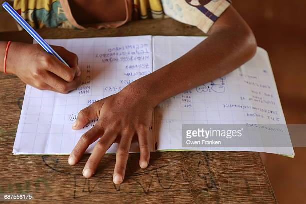 hands of a boy writing in a notebook