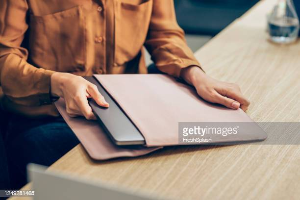 hands of a businesswoman taking out her laptop computer out of the sleeve on her desk - long sleeved stock pictures, royalty-free photos & images