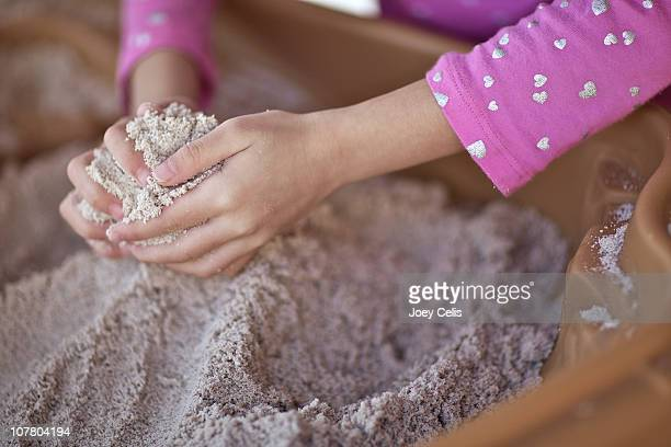 Hands of a child gathers sand