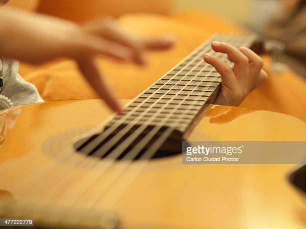 Hands of a child playing guitar