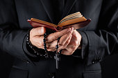 Hands of a christian priest dressed in black holding a crucifix and reading New Testament book.