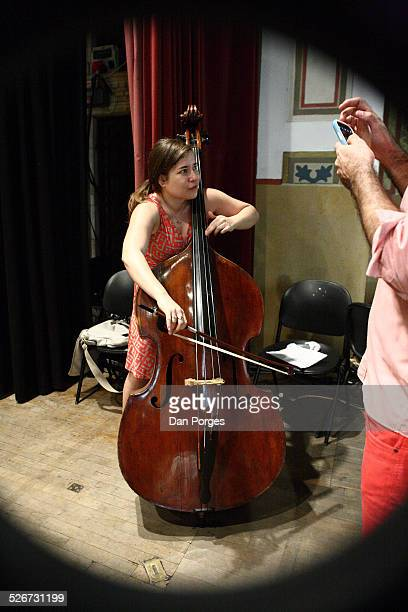 Hands of a colleague using a smartphone to photograph Alisa Weilerstein American cellist trying to play a double bass on stage of the Mary Nathaniel...