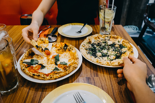 Hands of a couple sharing and enjoying freshly made pizza in an Italian restaurant - gettyimageskorea