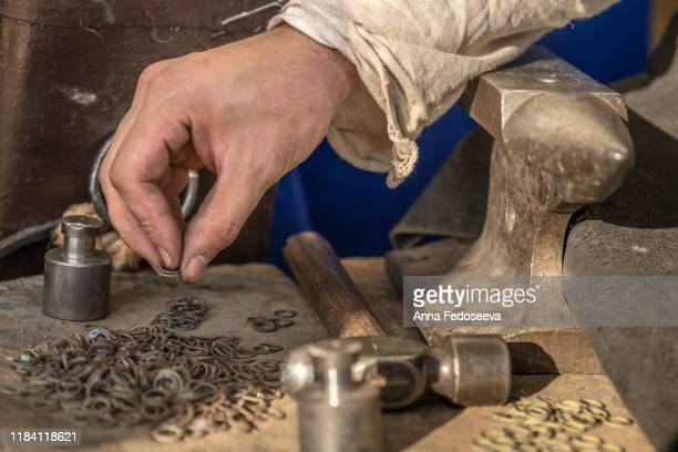 hands of a craftsman. a blacksmith holds metal rings with his hand. chain mail manufacture. old crafts. conducts a master class. workshop dressed in an old outfit. metal tools. - rpg maker stock pictures, royalty-free photos & images