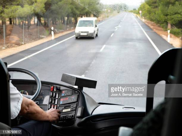 hands of a driver of bus to the steering wheel driving for a road of several rails with rain. - dashboard camera point of view stock photos and pictures